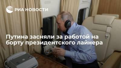 Путина засняли за работой на борту президентского лайнера перед встречей с Байденом